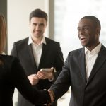 Smiling afro american businessman and caucasian businesswoman handshaking, first impression